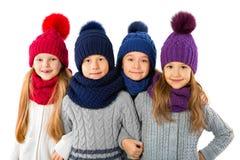 Groupe d'enfants mignons dans les chapeaux et des écharpes chauds d'hiver sur le blanc Vêtements d'hiver d'enfants Image stock