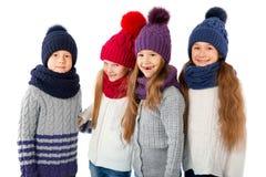 Groupe d'enfants mignons dans les chapeaux et des écharpes chauds d'hiver sur le blanc Vêtements d'hiver d'enfants Images stock