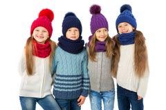 Groupe d'enfants mignons dans les chapeaux et des écharpes chauds d'hiver sur le blanc Vêtements d'hiver d'enfants Image libre de droits