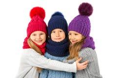 Groupe d'enfants mignons dans les chapeaux et des écharpes chauds d'hiver sur le blanc Vêtements d'hiver d'enfants Images libres de droits
