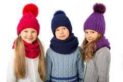 Groupe d'enfants mignons dans les chapeaux et des écharpes chauds d'hiver sur le blanc Vêtements d'hiver d'enfants Photographie stock libre de droits