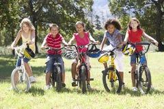 Groupe d'enfants montant des vélos dans la campagne Images libres de droits
