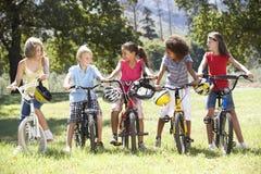 Groupe d'enfants montant des vélos dans la campagne Photo stock