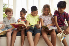 Groupe d'enfants multiculturels lisant sur le siège fenêtre photos libres de droits