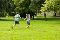 Groupe d'enfants ou d'amis heureux jouant dehors Photographie stock