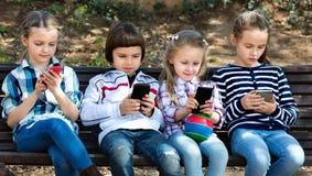 Groupe d'enfants posant avec des périphériques mobiles Image stock