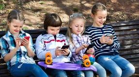 Groupe d'enfants posant avec des périphériques mobiles Photo stock