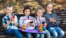 Groupe d'enfants posant avec des périphériques mobiles Photographie stock libre de droits