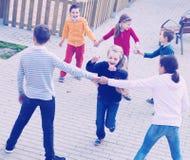 Groupe d'enfants positifs jouant le vagabond rouge Photos stock