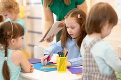 Groupe d'enfants préscolaires travaillant avec le papier, les sciccors et la colle de couleur sur la classe d'art dans le jardin  images libres de droits