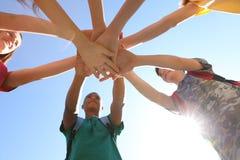 Groupe d'enfants remontant des mains dehors Image stock