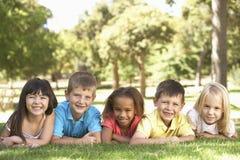 Groupe d'enfants s'étendant en parc image libre de droits