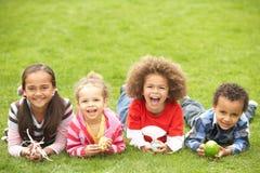Groupe d'enfants s'étendant sur l'herbe avec des oeufs de pâques