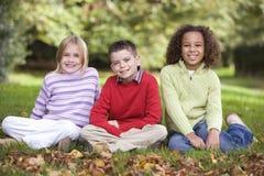 Groupe d'enfants s'asseyant dans le jardin Photographie stock