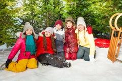 Groupe d'enfants s'asseyant sur la neige dans l'horaire d'hiver Photographie stock