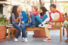 Groupe d'enfants s'asseyant sur le banc dans le mail Photos stock