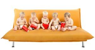 Groupe d'enfants s'asseyant sur le sofa, mangeant du maïs éclaté Photographie stock