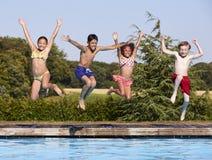 Groupe d'enfants sautant dans la piscine extérieure Photo libre de droits
