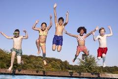 Groupe d'enfants sautant dans la piscine extérieure Photos stock
