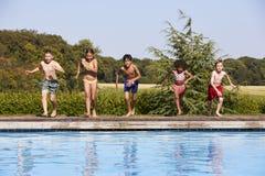 Groupe d'enfants sautant dans la piscine extérieure Photographie stock libre de droits