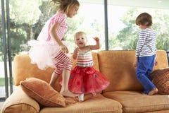 Groupe d'enfants sautant sur le sofa Photos stock