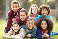 Groupe d'enfants se situant sur l'herbe ensemble en parc Photo libre de droits