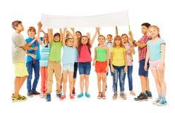 Groupe d'enfants se tenant avec la bannière vide blanche Photographie stock