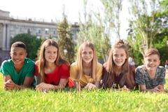 Groupe d'enfants se trouvant sur l'herbe dehors Photos libres de droits
