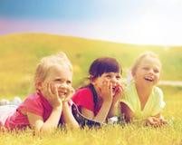 Groupe d'enfants se trouvant sur la couverture ou la couverture dehors Photos libres de droits