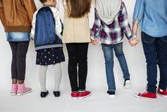 Groupe d'enfants tenant des mains derrière la vue arrière sur Blackgroun blanc Image stock