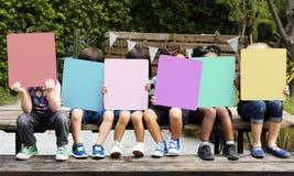 Groupe d'enfants tenant la couverture vide de bannière leur visage Image libre de droits