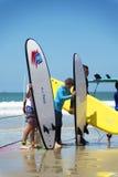 Groupe d'enfants tenant la planche de surf sur la plage Photo libre de droits