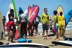 Groupe d'enfants tenant la planche de surf sur la plage Photographie stock libre de droits