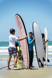 Groupe d'enfants tenant la planche de surf sur la plage Photos stock