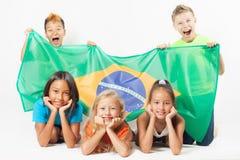 Groupe d'enfants tenant un drapeau du Brésil Image stock