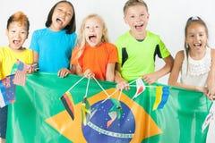 Groupe d'enfants tenant un drapeau du Brésil Photo stock