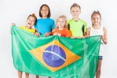Groupe d'enfants tenant un drapeau du Brésil Images stock
