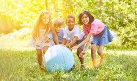 Groupe d'enfants tout en jouant avec le globe du monde Photographie stock libre de droits