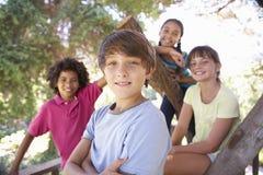 Groupe d'enfants traînant dans la cabane dans un arbre ensemble Images stock