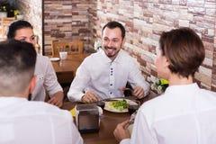 Groupe d'heureux amis mangeant au restaurant et à la causerie Images stock
