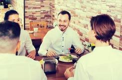 Groupe d'heureux amis mangeant au restaurant et à la causerie Photographie stock libre de droits