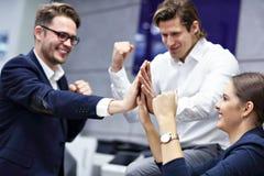 Groupe d'hommes d'affaires célébrant le succès dans le bureau photographie stock