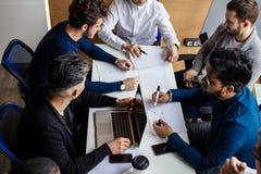 Groupe d'hommes d'affaires dans la salle de conférence moderne discuter des résultats de travail photos stock