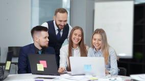 Groupe d'hommes d'affaires discutant travaillant au bureau moderne regardant et se dirigeant l'ordinateur portable d'écran banque de vidéos