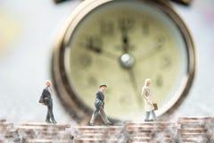 groupe d'hommes d'affaires miniatures marchant sur la pile de pièce de monnaie Photos stock