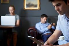 Groupe d'hommes d'affaires à l'aide des dispositifs de Digital en café image stock
