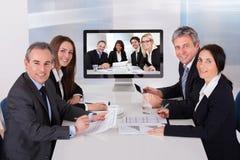Groupe d'hommes d'affaires dans la vidéoconférence Image stock