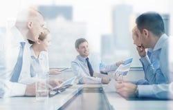 Groupe d'hommes d'affaires de sourire se réunissant dans le bureau Photographie stock libre de droits