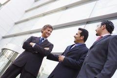 Groupe d'hommes d'affaires en dehors de l'immeuble de bureaux Image stock