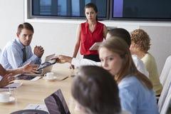 Groupe d'hommes d'affaires se réunissant autour du Tableau de salle de réunion photos stock